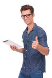Man holds tablet & shows thumb up. Casual young man holding a tablet in one hand and showing thumbs up with the other while smiling at you. isolated on a white Stock Photography
