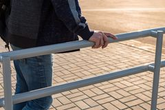 Man holds on to the handrail. Railing in front of highway. Improvement of city public services royalty free stock photo