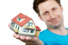Man holds toy house in outstretched hand Royalty Free Stock Photo