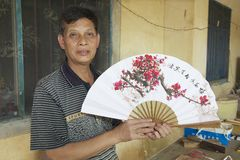 Man holds traditional Chinese fan in Yangshuo, China. Stock Images