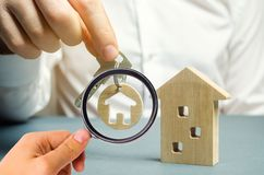 A man holds a trinket key with a house and a wooden home. Real estate concept. Realtor services. Sale of property. Buy housing. stock images