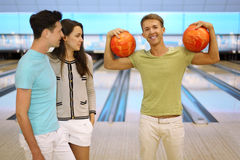 Man holds two balls; pair look at him Stock Photos