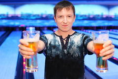 Man holds two glasses of beer in bowling club Royalty Free Stock Photography