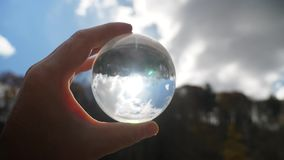 Man holds up lens sphere to sun. A man holds up a lens sphere in front of the sun stock footage