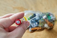 A man holds used batteries to throw in a plastic bottle, the topic of sorting garbage stock photography