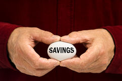 Man holds white egg with SAVINGS written on it stock photo