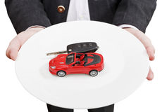 Man holds white plate with red car and key Stock Image