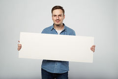 Man holds the white sign in a studio white background Royalty Free Stock Photo