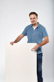 Man holds the white sign in a studio white background Royalty Free Stock Image