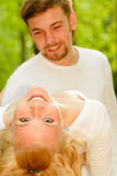 Man holds woman. Young beautiful pair in white clothes jokes and is played in a summer garden Royalty Free Stock Image