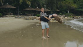 A man holds a woman in her arms, a young couple in love swirl on the sea beach. The concept of a happy family and rest stock video