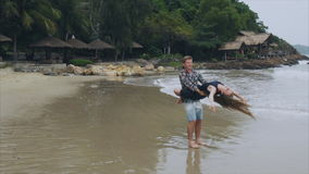 A man holds a woman in his arms, a young couple in love swirl on the sea beach in slow motion. The concept of a happy stock footage