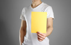 A man holds a yellow paper in his hand. Shows a blank flyer. Stock Image