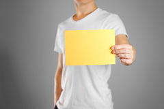A man holds a yellow paper in his hand. Shows a blank flyer. Stock Images