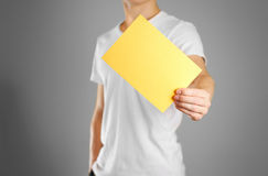 A man holds a yellow paper in his hand. Shows a blank flyer. Royalty Free Stock Image