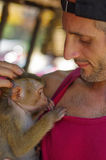 Man holds a young Rhesus Macaque Macaca mulatta on the armp, potrait. Royalty Free Stock Photo