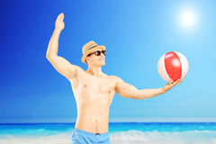 Man on a holiday, playing with ball next to a sea Stock Images