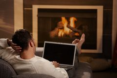 Man at home. Man sitting on sofa at home in front of fireplace and using laptop computer, rear view Stock Photography