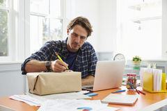 Man At Home Addressing Package For Mailing Royalty Free Stock Photography