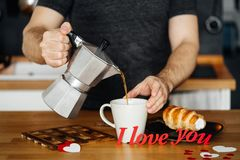 Man in home clothes pours hot coffee into a mug with the words I LOVE YOU from red paper on the table with a cake, against the bac. A man in home clothes pours stock photography