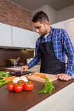 Man in home kitchen looking recipe with a Stock Image