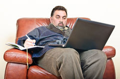 Man at home laptop writing Royalty Free Stock Photos