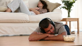 Man at Home listening to music on the ground Stock Images