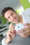 Man at home looking at message on smartphone Royalty Free Stock Image