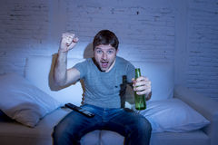 Man at home lying on couch at living room watching sport match on tv holding beer bottle celebrating goal Royalty Free Stock Photography