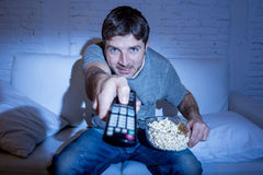Man at home lying on couch at living room watching tv eating popcorn bowl using remote control. Young attractive man at home lying on couch at living room Stock Image