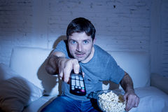 Man at home lying on couch at living room watching tv eating popcorn bowl using remote control Royalty Free Stock Photo