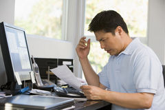 Man in home office with computer and paperwork royalty free stock photography