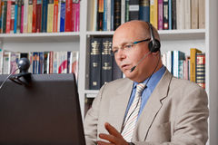Man in home-office talking via skype. Man in home office talking with colleague via skype, copyspace Stock Photo
