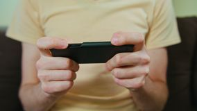 Man in Home Play Game on Smartphone stock images