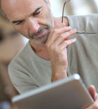 Man at home reading ebook on tablet Stock Photo