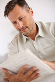 Man at home relaxing and reading newspaper Stock Photography