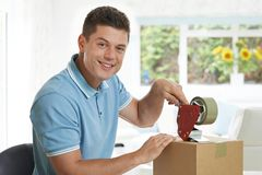 Portrait Of Man At Home Sealing Box For Dispatch royalty free stock photos