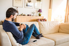 Man at home sitting on sofa using smart watch Royalty Free Stock Images