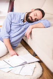 Man at home. Man is sleeping while sitting on the floor at home with documents Royalty Free Stock Images