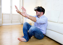 Man at home sofa couch excited using 3d goggles watching 360 vir Royalty Free Stock Photo