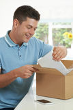 Man At Home Unwrapping Digital Tablet Bought Online Stock Photography