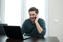 Man at home working on a laptop. Portrait of a smiling man working on a laptop at home and talking on the phone stock photos