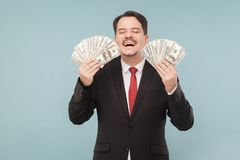 Man honestly earned a lot of money. Indoor, studio shot, isolated on light blue or gray background Stock Image