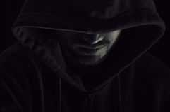 Man with hood. Scary man with a hood sitting  in the dark Stock Photo