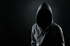 Man in the hood. Silhouette of hooded man or hooligan over dark, concrete background Stock Image