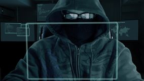 Man in hood glasses and mask of balaclava sits at the computer laptop and downloads secret data. A hacker at night hack