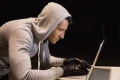 Man in hood jacket hacking a laptop Stock Image