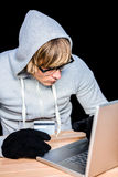 Man in hood jacket hacking a laptop Royalty Free Stock Image