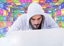 Man in hood on laptop in front of icons. Digital composite of Man in hood on laptop in front of icons stock images