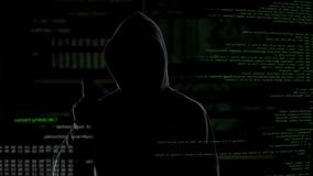 Man in hood push button on virtual screen with scripts, anonymous cyber attack. Stock footage stock footage